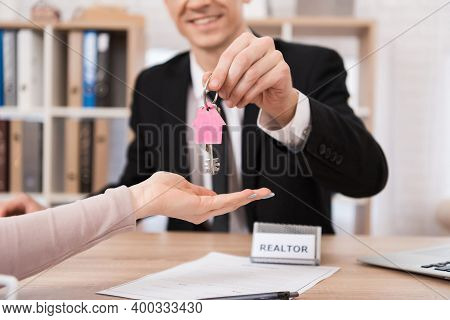 Realtor Shows The Numbers On The Calculator While Sitting In The Office. Realtor With A Calculator C