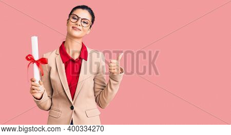 Young beautiful woman wearing glasses holding graduate degree diploma smiling happy and positive, thumb up doing excellent and approval sign