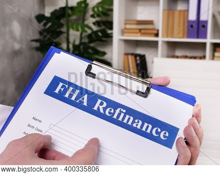 The Hand Points To A Fha Refinance For Signing.