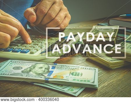 Payday Advance Loan Concept. Calculator And Wads Of Money.