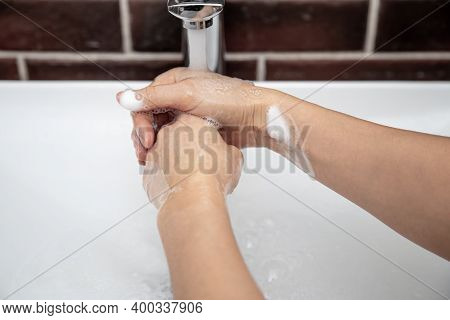 Washing Hands With Soapy Water Under Running Water. The Concept Of Personal Hygiene And Health.