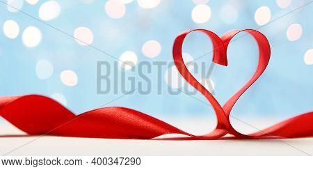 Red Ribbon In Heart Shape On Blue Background