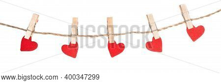 Clothes Pegs And Red Wood Hearts On Rope Isolated On White Background