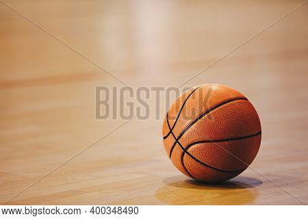 Orange Basketball Ball On Wooden Parquet. Close-up Image Of Basketball Ball Over Floor In The Gym