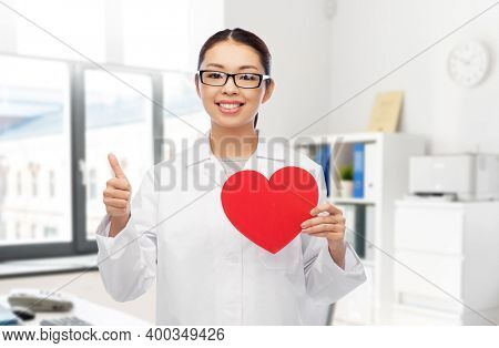 medicine, cardiology and healthcare concept - happy smiling asian female cardiologist doctor or nurse with red heart showing thumbs up over hospital background