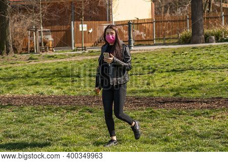 Prague, Czech Republic. 03-11-2020. Young Woman Walking While Checking Her Cellphone In Park Stomovk