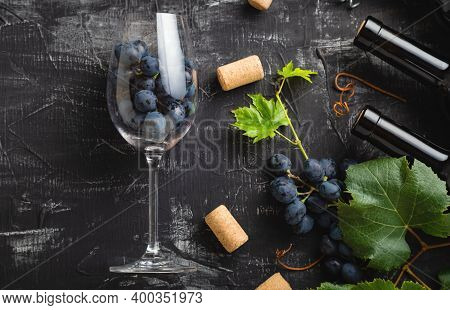 Wine Glass Full Of Grapes Inside. Wine Bottles, Grape Bunches With Leaves And Vines Wine Corks On Da