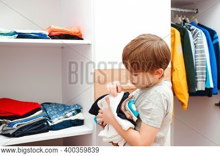 Boy Organizing Clothes In Wardrobe, Close Up. Kid Putting Stack Of Clothes On The Shelf.