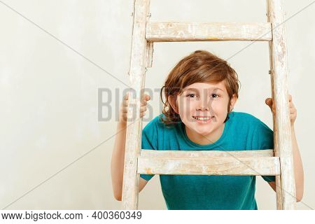 Happy Kid Looks Through Ladder. New House For Family. Home Renovation.