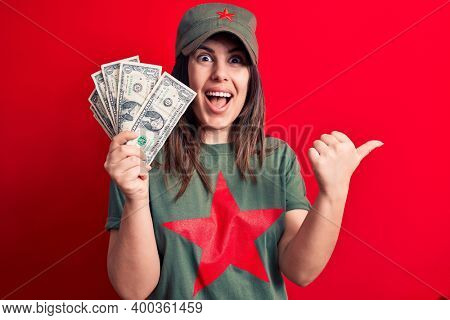 Woman wearing t-shirt with red star communist symbol holding bunch of dollars banknotes pointing thumb up to the side smiling happy with open mouth