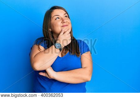 Beautiful brunette plus size woman wearing casual blue t shirt with hand on chin thinking about question, pensive expression. smiling with thoughtful face. doubt concept.