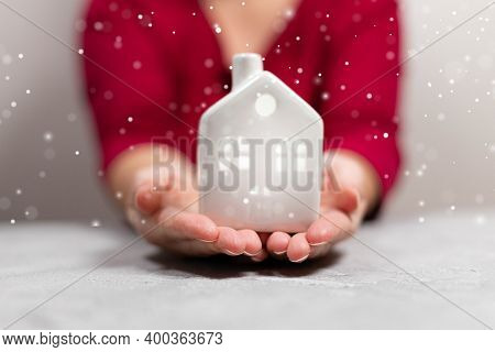 Female Hands Hold Small Cozy House On A Gray Background. Christmas Banner.