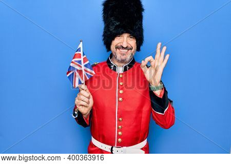 Middle age handsome wales guard man wearing traditional uniform holding united kingdom flag doing ok sign with fingers, smiling friendly gesturing excellent symbol