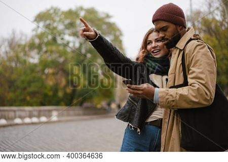 Multinational beautiful couple pointing finger aside and using mobile phone at city street