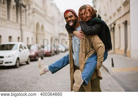Happy afro american man giving piggyback ride his laughing girlfriend at city street