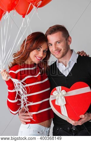 Couple with heart shaped balloons and gift, Valentines day concept