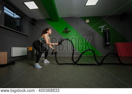 Young Fit Woman Doing Exercise With Battle Ropes In Training Class. Functional Training, Workout Pro