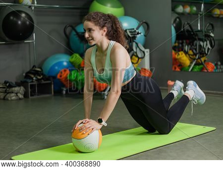Young Fit Woman Doing Push Up Exercise With Medicine Ball In Sports Class. Training Process