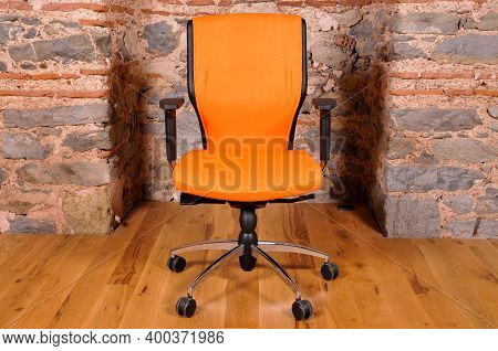 Comfortable And Stylishly Designed Orange Office Chair In Front Of A Wall