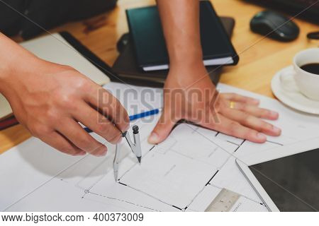 Engineer Or Architect Using Divider Compass Tools On Blueprint In Office On Site.