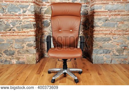 Comfortable And Stylishly Designed Brown Office Chair In Front Of A Wall