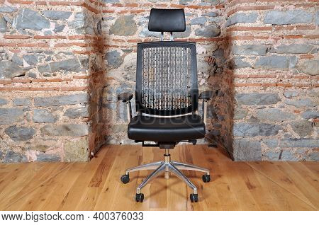 Comfortable And Stylishly Designed Black Office Chair In Front Of A Wall