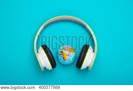 World Song. Global Music Chart. The Music Of Earth. Stereo Headphones And Globe On Blue Background.