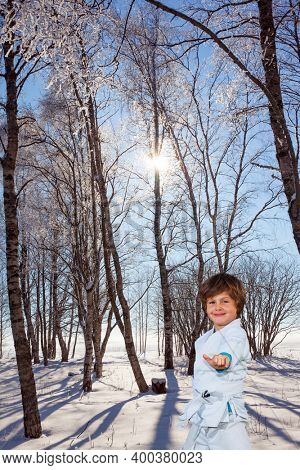 Handsome boy training for judo. New Years is soon. Frosty snowy sunny day in the winter forest. The northern winter sun is low above the horizon