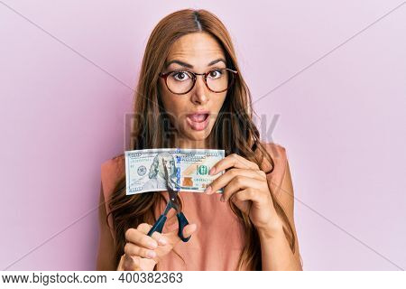 Young brunette woman cutting dollars with scissors for currency devaluation in shock face, looking skeptical and sarcastic, surprised with open mouth