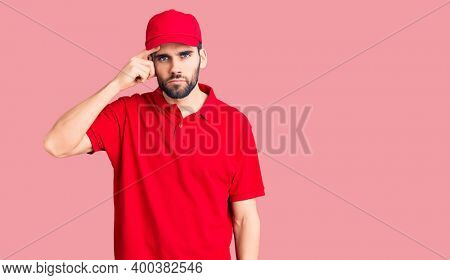 Young handsome man with beard wearing delivery uniform pointing unhappy to pimple on forehead, ugly infection of blackhead. acne and skin problem