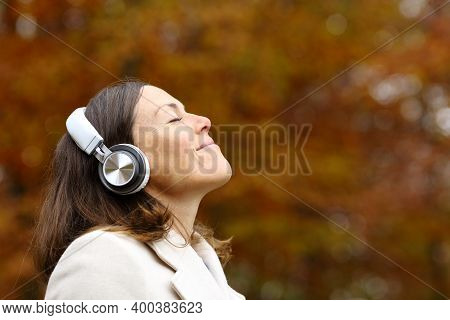 Adult Woman Breathing Fresh Air With Headphones In A Park In Autumn