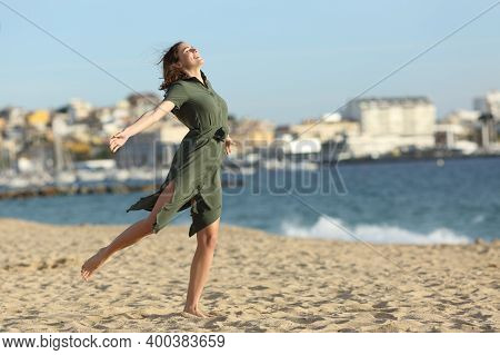 Full Body Portrait Of A Happy Woman Wearing Dress Celebrating Summer Vacation On The Beach