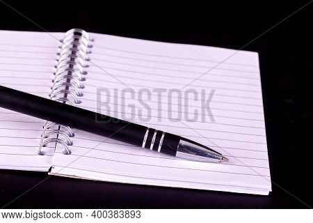Pen And Opened A5 Notepad With White Lined Pages And Spiral Boound With A Black Background