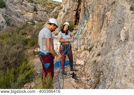Couple Of Climbers Prepares The Knots And Belays To Start Climbing While The Girl Climber Looks On S