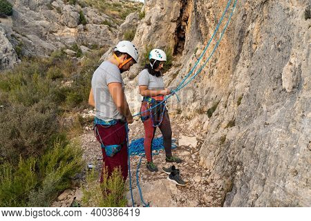Couple Of Climbers Are Concentrated Preparing The Knots And Belays To Start Climbing