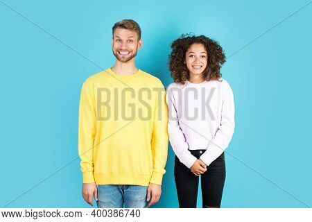 Two Funny And Mixed Race People Making Silly Faces While They Standing Together On Blue Background W