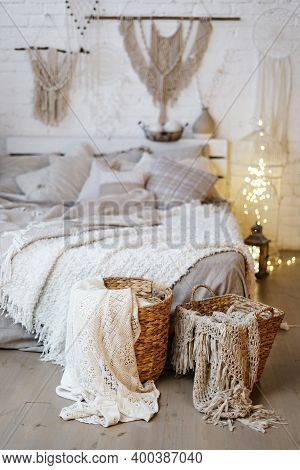 Vertical Photo Of Wicker Basket With Textile Standing Near Comfortable Bed Against Blurred Cozy Bedr