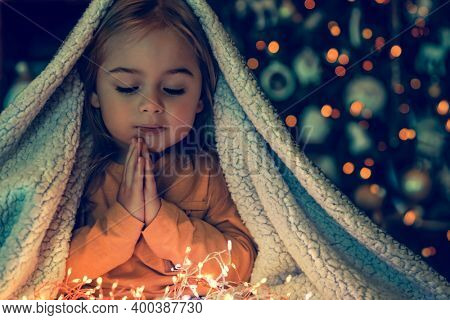 Kid Making Magic Wish for Winter Holidays. Baby Near the Christmas Tree at Home. Under the Plaid Praying. Waiting for Santa at Night.