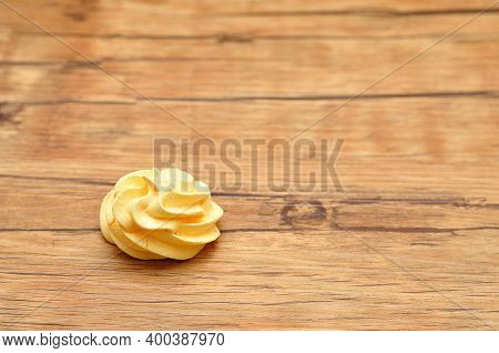A Yellow Meringue On A Wooden  Table