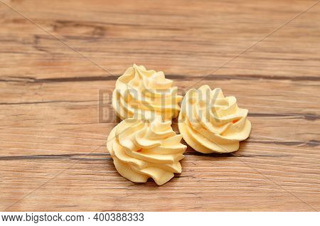 Three Yellow Meringues On A Wooden  Table