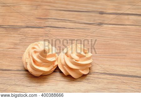 Two Orange Meringues On A Wooden Table