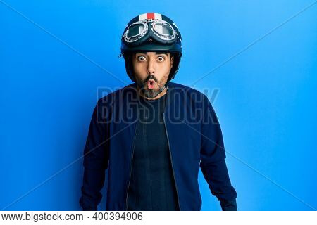 Young hispanic man holding motorcycle helmet scared and amazed with open mouth for surprise, disbelief face