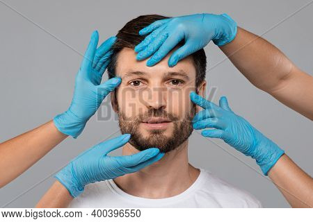 Plastic Surgeon Hands In Protective Medical Gloves Touching Middle-aged Man Face On Grey Studio Back