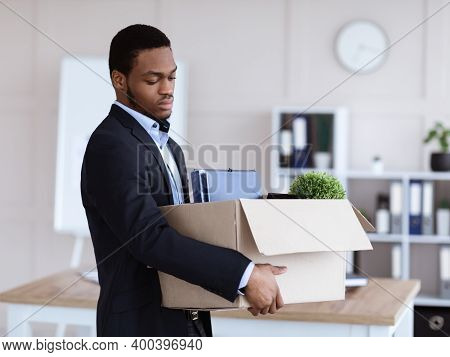 Upset Black Man Got Fired, Standing In Office And Holding Box With His Belongings, Copy Space. Termi