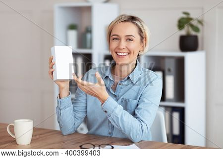 Young Female Blogger Recording Video Review Of New Modern Device, Demonstrating Tech Product At Home