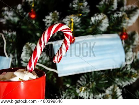 Close Up Red Cup With Sweet Caramel Cane And Marshmallows On The Background Of Christmas Tree With P