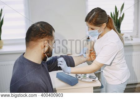 Nurse Taking Blood Sample From Patient At The Doctors Office