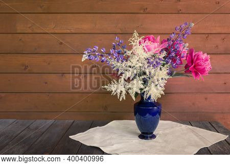 Beautiful Bouquet Made Of Astilbe, Lupine And Peonies In Blue Vase On Rustic Wooden Table. View With