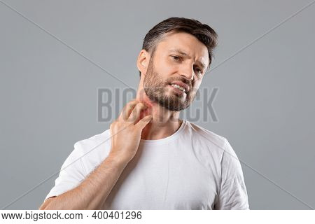 Middle Aged Bearded Man Scratching Highlighted With Red Neck On Grey Studio Background, Copy Space.