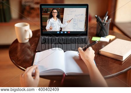 Online Course Concept. Point Of View Of Female Student Sitting At Table, Writing In Notebook, Taking